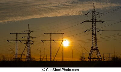 High-voltage power lines at sunset. Fuel and power...