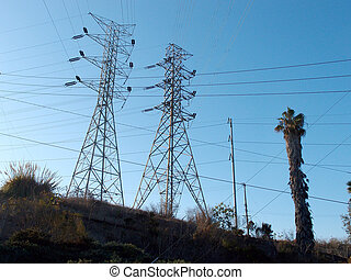High Voltage Power Lines intersect at two large metal Utility pole