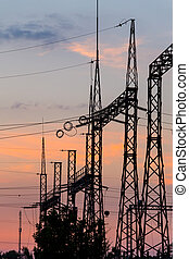 High voltage power plant at sunset
