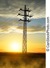 High voltage power pylon at sunset.