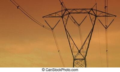 high voltage pylons at sunset. 30 fps