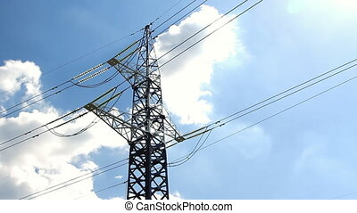 High voltage tower and cables against blue sky