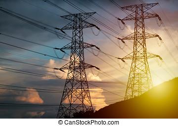 High Voltage Tower on hillside during sunset