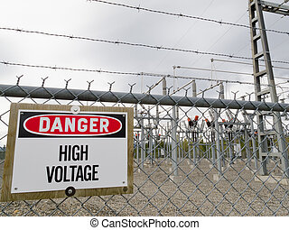 High-voltage transformer substation behind barbed-wire...