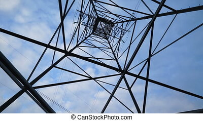 High voltage transmission tower against the sky tilt down....