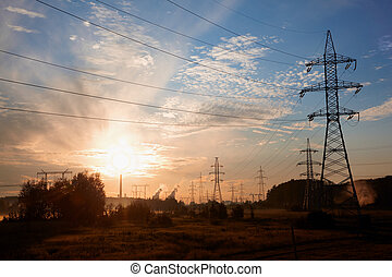 High-voltage transmission towers in the suburbs at sunrise