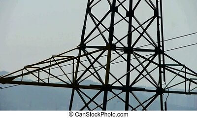 High-voltage wire tower in urban city,distant mountain &...