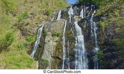 High Waterfall Cascade Runs down among Rocks in Highland