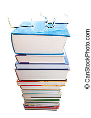Higher Learning - A huge stack of text books with a pair of...