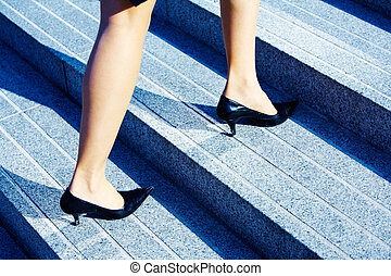Higher Level - Businesswoman walking up stairs to higher...