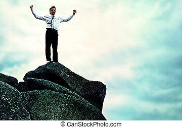 highest achievement - Successful business man standing on a...