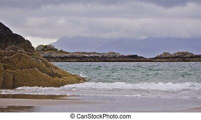 Highlands landscape in Scotland, UK - Waves rolling in at...