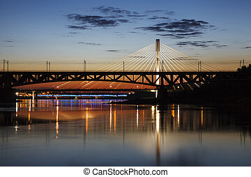 Highlighted bridge at night and reflected in the water