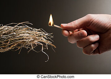 highly flammable - male hand holding a match in the act of...