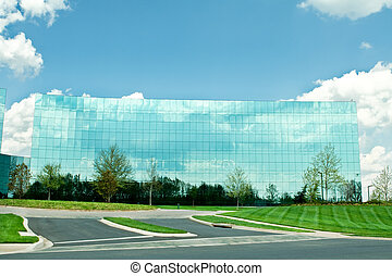 Highly reflective glass office building in Maryland, USA .  Blue sky with puffy white clouds.