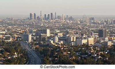 Highrise skyscrapers of metropolis and busy rush hour highway, Los Angeles, California USA. Urban downtown skyline and traffic jam. Aerial view of cityscape and cars on driveway. Freeway in LA city