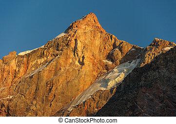 Hight scarlet mountain peak in sunset rays