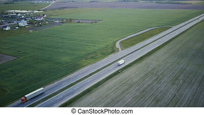 Highway aerial panorama with field and village. Drone 4K...