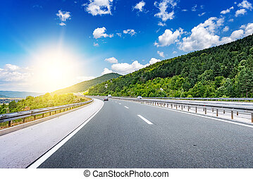 Highway among the mountain scenery in the sun rays.