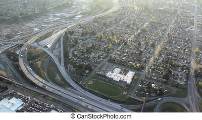 Highway and Neighborhood - Aerial - Bright sunrise over...