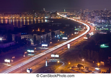 Highway at night in modern city. Aerial view of cityscape