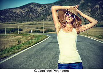 highway - Beautiful young woman posing on a road over ...
