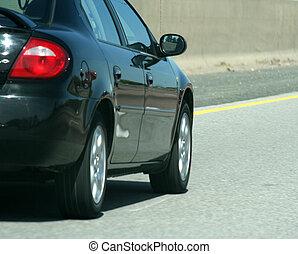 A black car speeding on the highway.