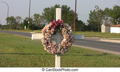 Highway Cross - A white cross with a flower wreath hanging...