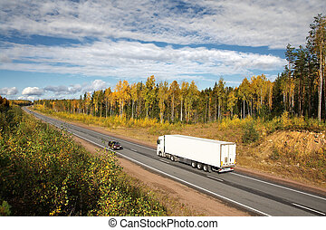 white truck on autumn highway, landscape