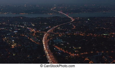 Highway Freeway Road going through Istanbul City with Red Illuminated Bosphorus Bridge in the distance at Night, Aerial Wide View