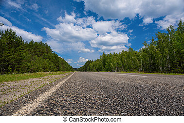 Highway in the forest with sky and clouds.