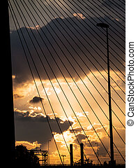 Highway, lightpost, chimney bridge silhouettes at sunset