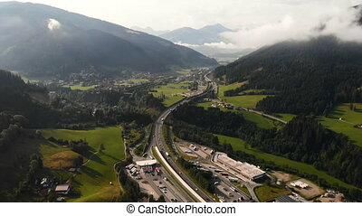 Driving freeway highway road country village forest in the mountains. Summer sky with clouds. Aerial drone view.
