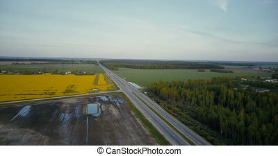 Highway road in valley with forest canola field. Aerial...