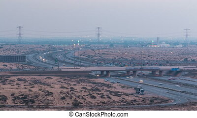 Highway roads with traffic day to night timelapse in a big city from Ajman to Dubai before sunset. Transportation concept.