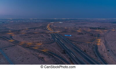 Highway roads with traffic night to day timelapse in a big city from Ajman to Dubai before sunrise. Transportation concept.