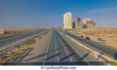 Highway roads with traffic timelapse in a big city from Ajman to Dubai before sunset. Transportation concept.