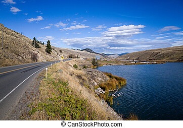 Highway skirting a scenic mountain lake