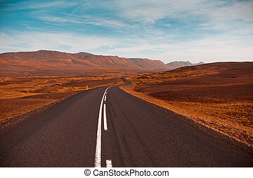 Highway through dry gravel lava field landscape under a blue summer sky. Highlands of Central Iceland. Filtered image