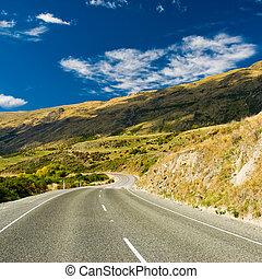 highway through hills somewhere in new zealand