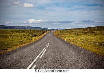 Highway through Icelandic landscape under a blue summer sky...