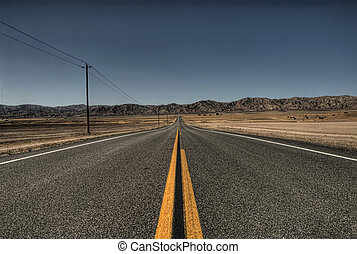 A two lane blacktop highway leads straight into the hills.