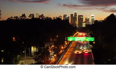 Rush hour cars and trucks travel on down the road as the light fades in Southern California