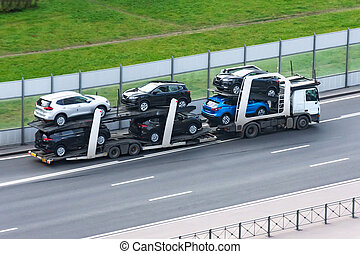 Highway transportation of new cars on a trailer with a truck for delivery to dealers.
