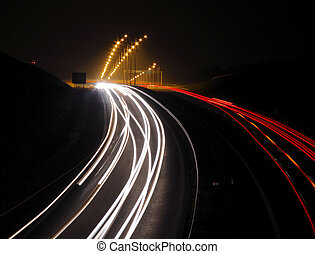 Highway with car lights trails at night.