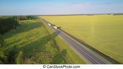 highway with driving trucks lorries between field and groves...