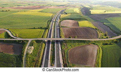 Highway with traffic in rural scenery. Suburban highway with cars and trucks. Travel and transportation. Aerial view. High quality 4k footage