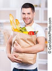 hij, is, innige, over, gezonde , voedsel., vrolijke , jonge man, vasthouden, winkeltas, volle, van, kruidenierswaren, terwijl, staand, in de keuken