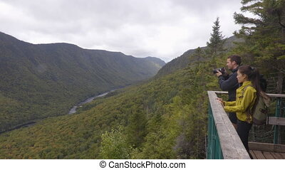Hike couple camping with backpacks in Quebec National Park in Autumn season, Canada forest travel lifestyle. Tourists looking at view of Jacques Cartier National Park.