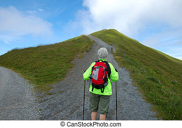 Hiker Alone - Middle-aged woman hiker with backpack facing a...